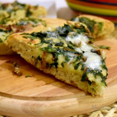 Pizza gustosa e croccante con spinaci e acciughe